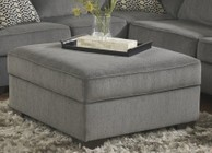 Ashley 1270011 Loric Ottoman with Storage  Cup Holders  Plush Cushion  Tapered Legs  Low Melt Fiber Wrapped Over Foam and Fabric Upholstery in Smoke Color