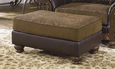 Ashley 3460214 Wilmington Ottoman with Faux Leather Upholstery  Fabric Cushioned Seat and Wide Turned Legs in Walnut